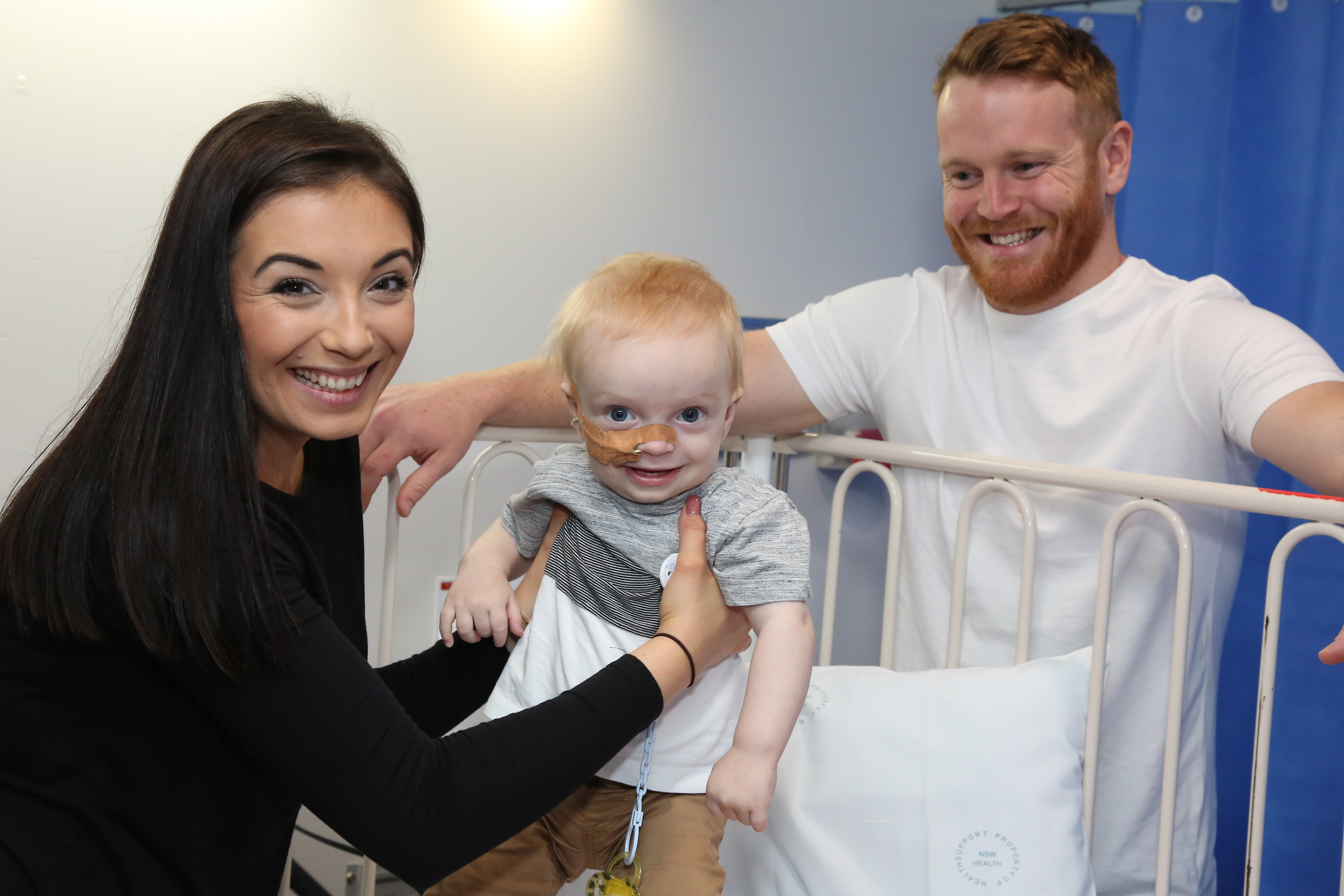 Parents with child in hospital smiling