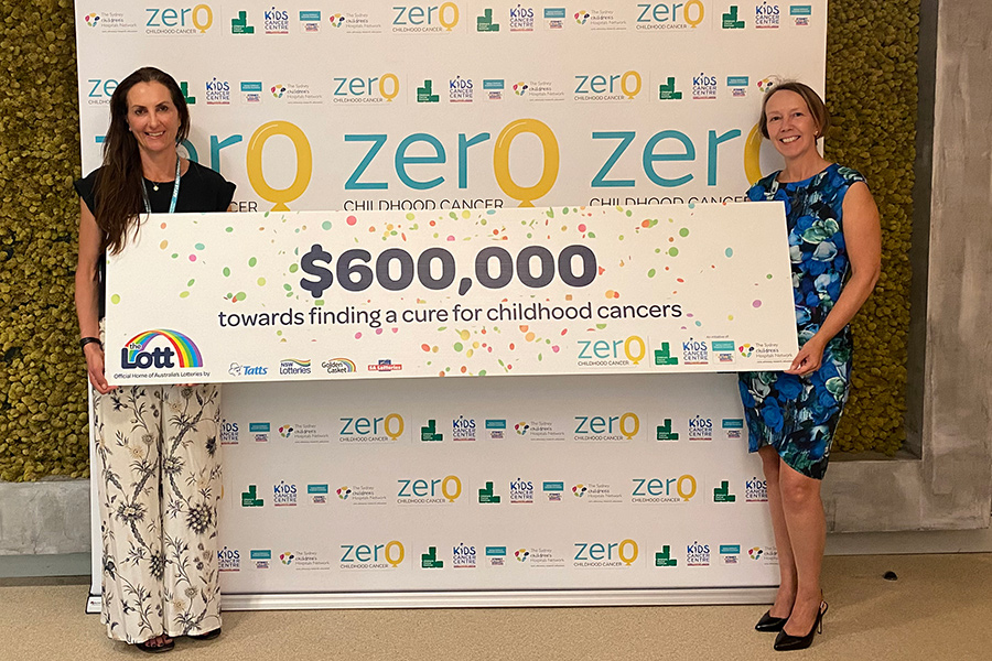 Two women holding $600,000 cheque