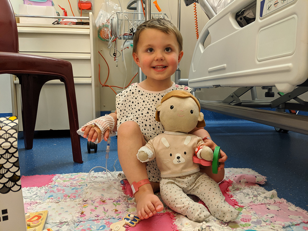 young girl smiling in hospital with her doll